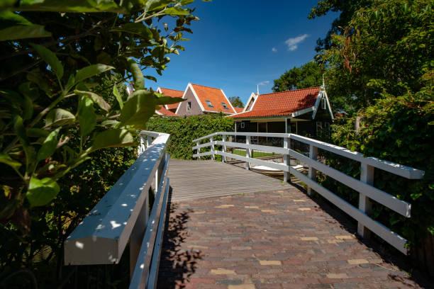witte houten fietser of footbridge in een oude traditionele nederlandse dorp met een groene klinker pad, hedge funds en straatverlichting - beemster stockfoto's en -beelden