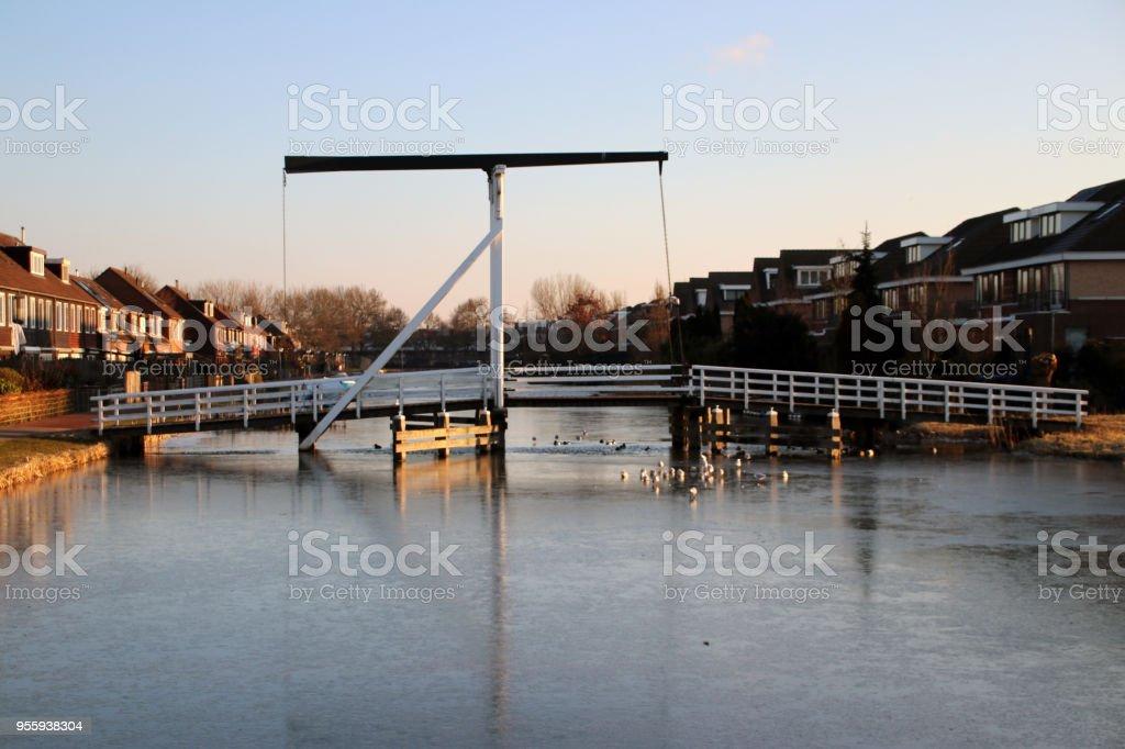 Witte houten ophaalbrug in het centrum van het dorp Nieuwerkerk aan den IJssel over de ring kanaal Zuidplaspolder met ijs in de ochtendzon foto