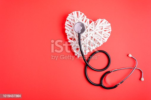 White wooden heart with black stethoscope on red paper background. Heart health concept. Top view. Flat lay. Copy space