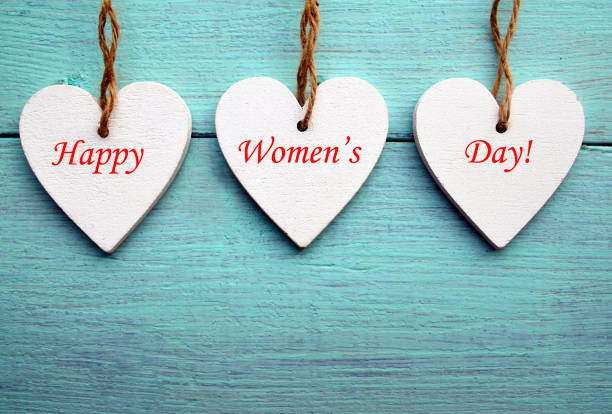 white wooden hearts on a blue wooden background.happy women's day. - womens day stock photos and pictures