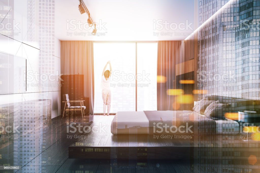 White wooden loft bedroom with a TV set, woman royalty-free stock photo