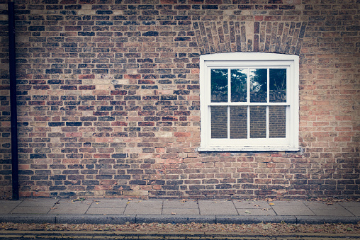 White wooden sash window on a restored brick wall of a Victorian house residential building. Vintage effect