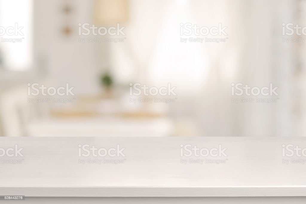 White wooden table and blurred dining room