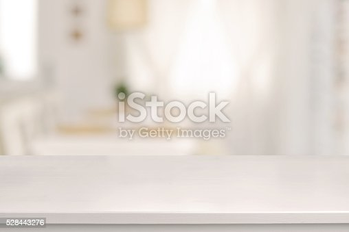 Empty white wooden table and blurred dining room interior decoration background. Product display. Sun is shining trhough the window.