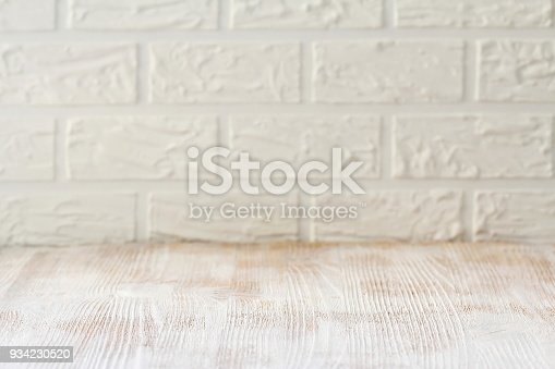 istock White wooden table with a brick wall as a background 934230520