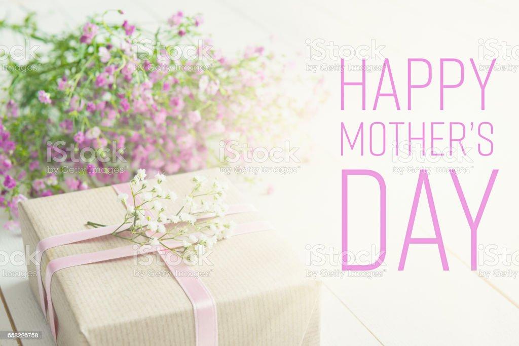 Weißer Holztisch mit rosa Blumen und ein Geschenk – Foto