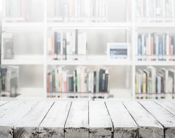 weiße holz textur tischplatte auf unschärfe bibliothek hintergrund. - vorschuldekorationen stock-fotos und bilder