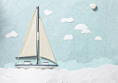 White wooden toy sailing boat on light blue paper background
