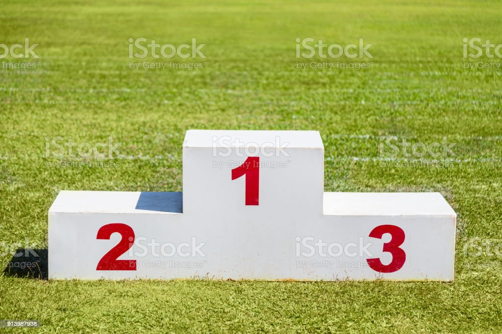 White wooden winner podium, with red winner number 1, 2 and 3 painted on, placed on green grass sport field, top empty space for text stock photo