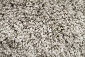 Background of beige carpet with black abstract spots. The texture of the surface fabric of the rope mat is brown
