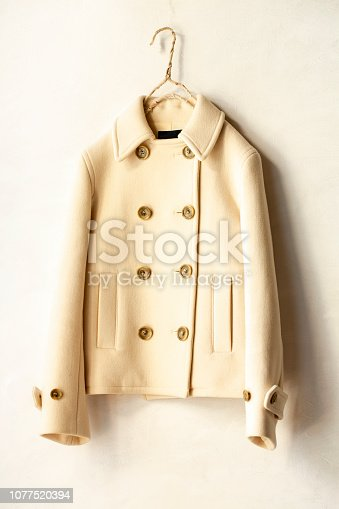 white wool short coat hanging on clothes hanger on white background