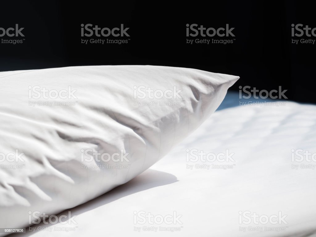 White wrinkles dust mites pillow and bedding cover with black background in the bedroom. stock photo