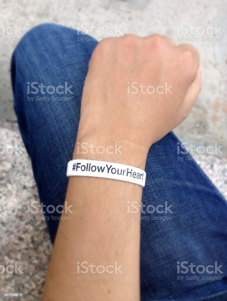 White wristband in wrist, hand on blue jeans. stock photo