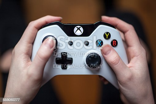 Gothenburg, Sweden - January 17, 2015: A close up shot from above of a young woman's hands holding a white Xbox One controller as she is playing a video game. Natural lighting, shot on wooden background with shallow depth of field.