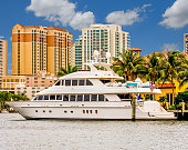 A large white yacht on a canal in front of a condominium