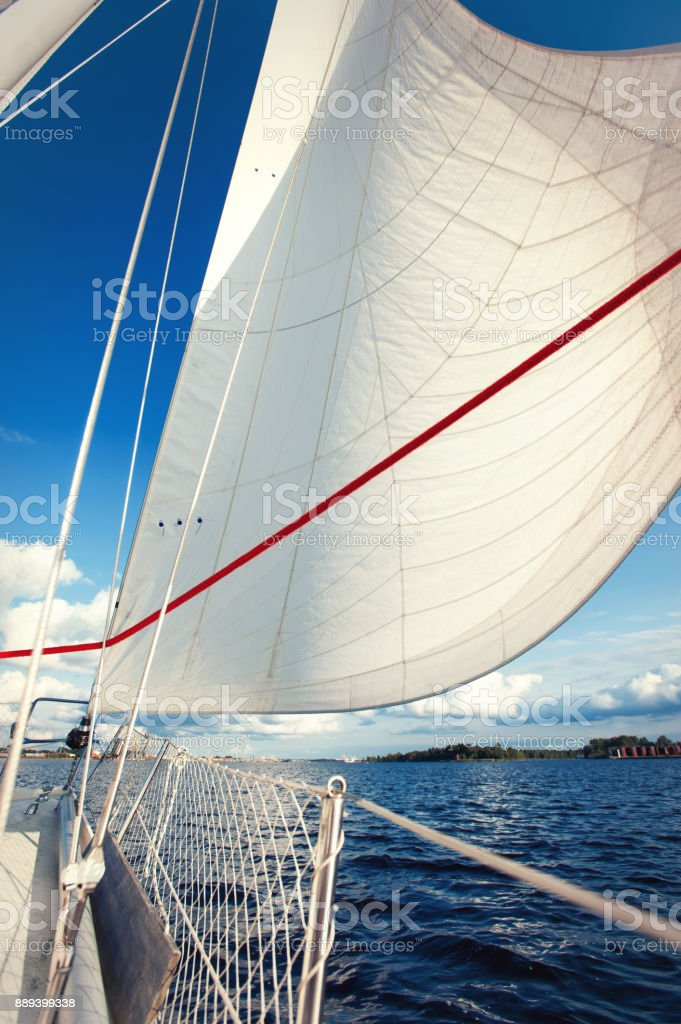 White yacht drifting in sunlight on blue cloudy sky background. stock photo