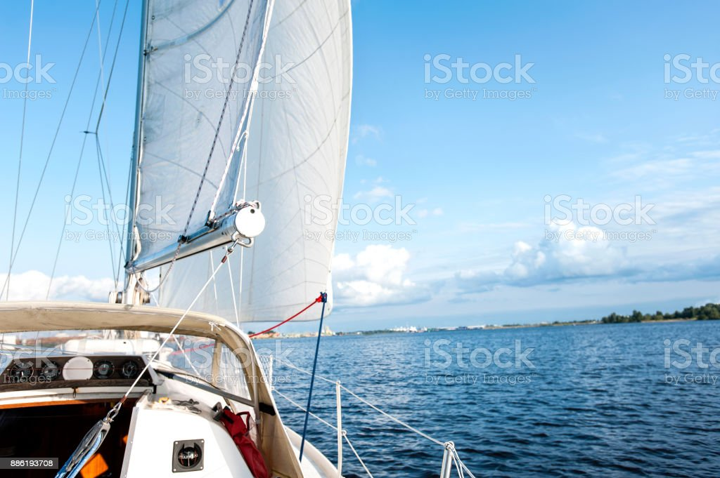 White yacht drifts in sunlight on blue cloudy sky background. stock photo