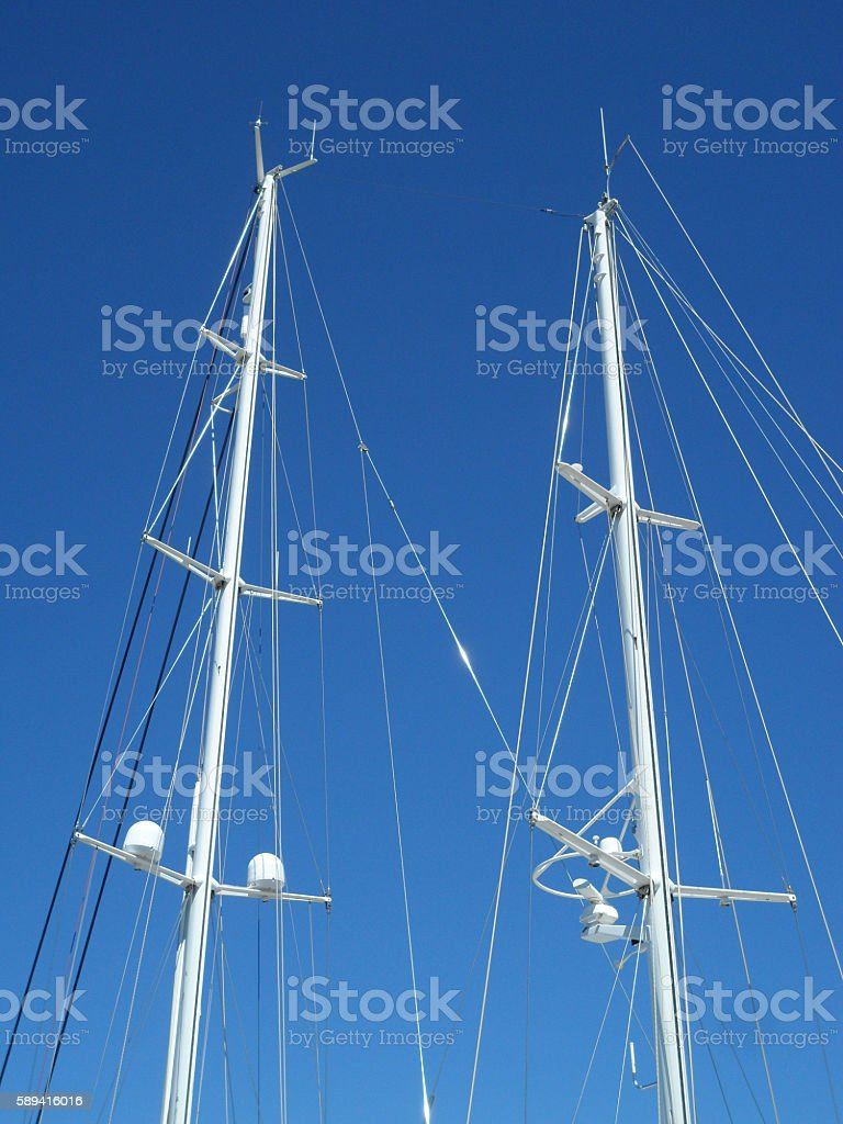 White Yacht Masts Against Clear Blue Sky stock photo