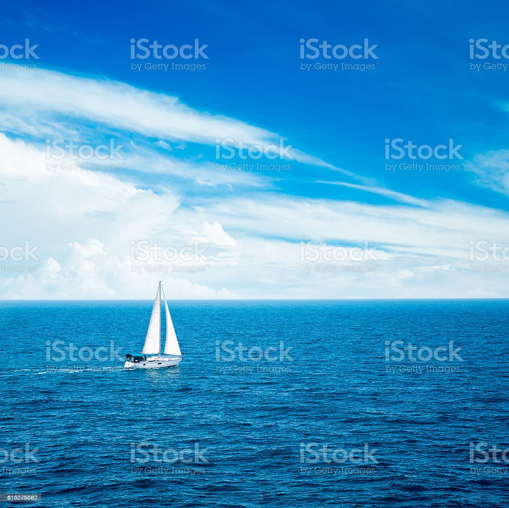 White Yacht Sailing in Blue Sea. stock photo