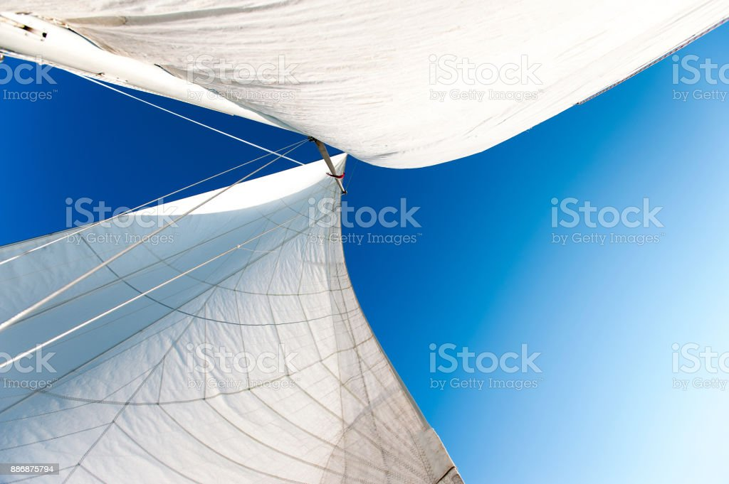 White yacht sails in sunlight on blue cloudy sky background. stock photo