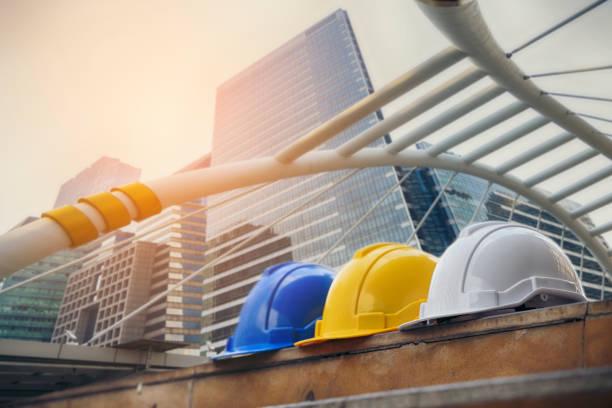Weißer, gelber und blauer Hartsicherheitshut für das Sicherheitsprojekt des Arbeiters als Ingenieur oder Arbeiter, auf dem Betonboden auf der Stadt. – Foto