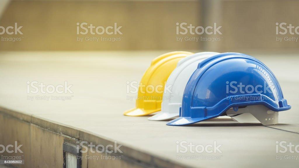weiß, gelb und blau hart Sicherheit Helm Hut für Sicherheit-Projekt des Arbeiters als Ingenieur oder Arbeiter, auf Betonboden auf Stadt – Foto