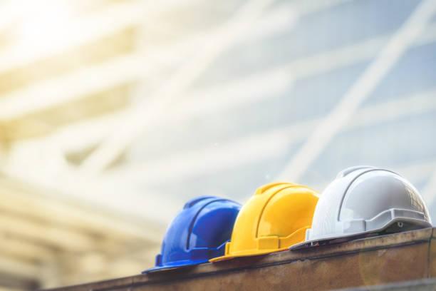 weiß, gelb und blau hart Sicherheit Helm Hut für Sicherheit-Projekt des Arbeiters als Ingenieur oder Arbeiter, auf Betonboden auf Stadt. – Foto