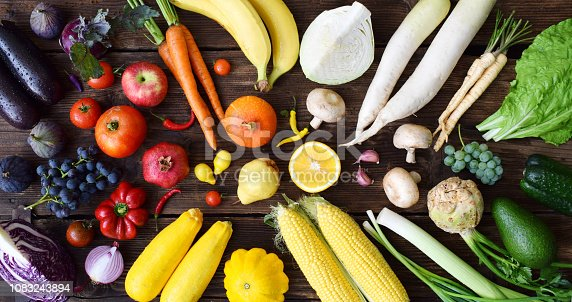 White, yellow, green, orange, red, purple fruits and vegetables on wooden background. Healthy food. Multicolored raw food
