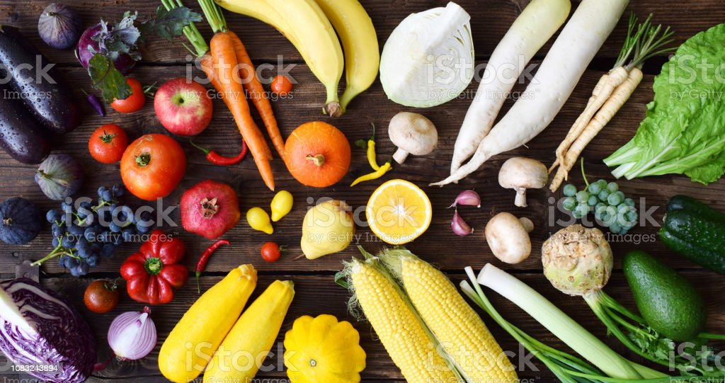 White, yellow, green, orange, red, purple fruits and vegetables on wooden background.  Healthy food. Multicolored raw food. stock photo