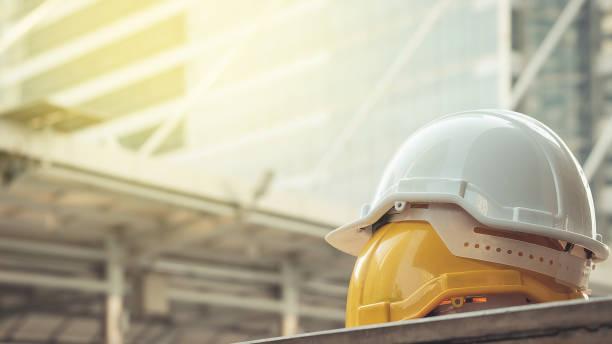 biały, żółty kask ochronny do projektu bezpieczeństwa robotnika jako inżyniera lub pracownika, na betonowej podłodze na mieście - kask ochronny odzież ochronna zdjęcia i obrazy z banku zdjęć