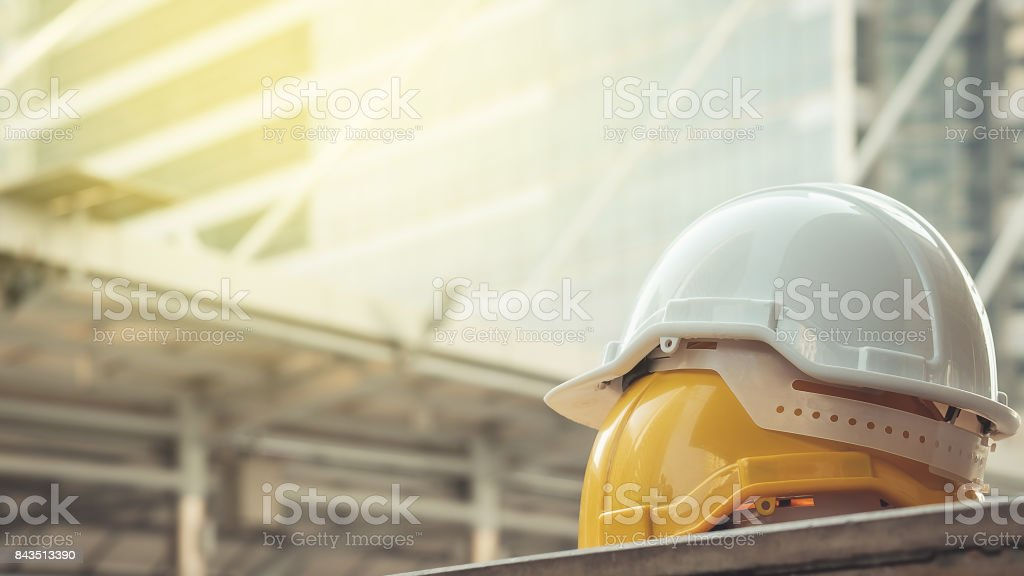 white, yellow hard safety helmet hat for safety project of workman as engineer or worker, on concrete floor on city stock photo