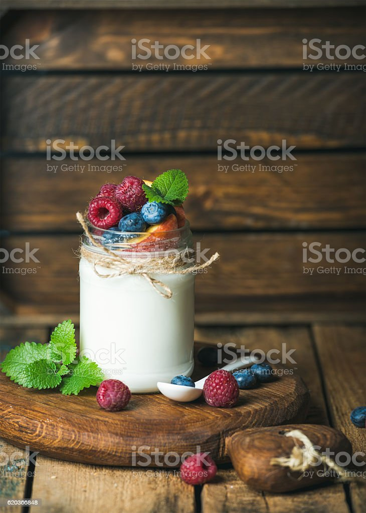 White yogurt with fresh berries, peach and mint leaves foto de stock royalty-free