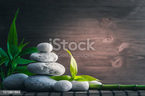 white zen  balance stones and bamboo plant on the wooden table