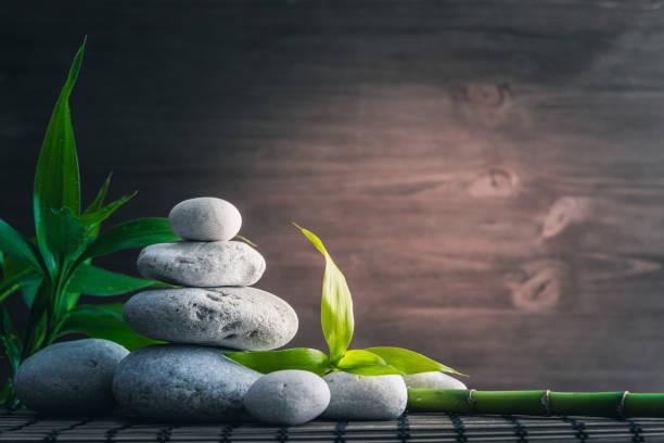 weißen zen gleichgewicht steinen und bambuspflanze auf dem holztisch - feng shui einrichten stock-fotos und bilder
