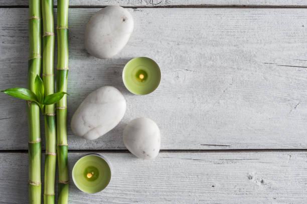 weißen zen gleichgewicht steinen, bambuspflanze auf dem holztisch - feng shui einrichten stock-fotos und bilder
