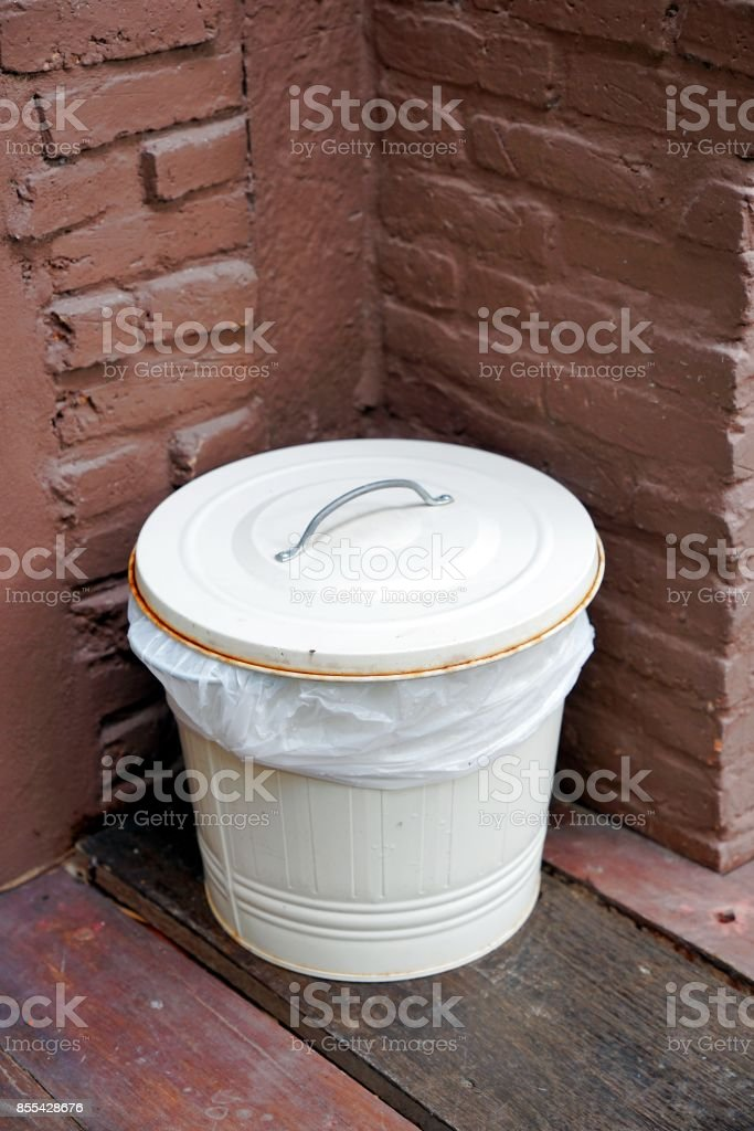 White Zinc bucket bin with lid and plastic bag inside in the corner. stock photo