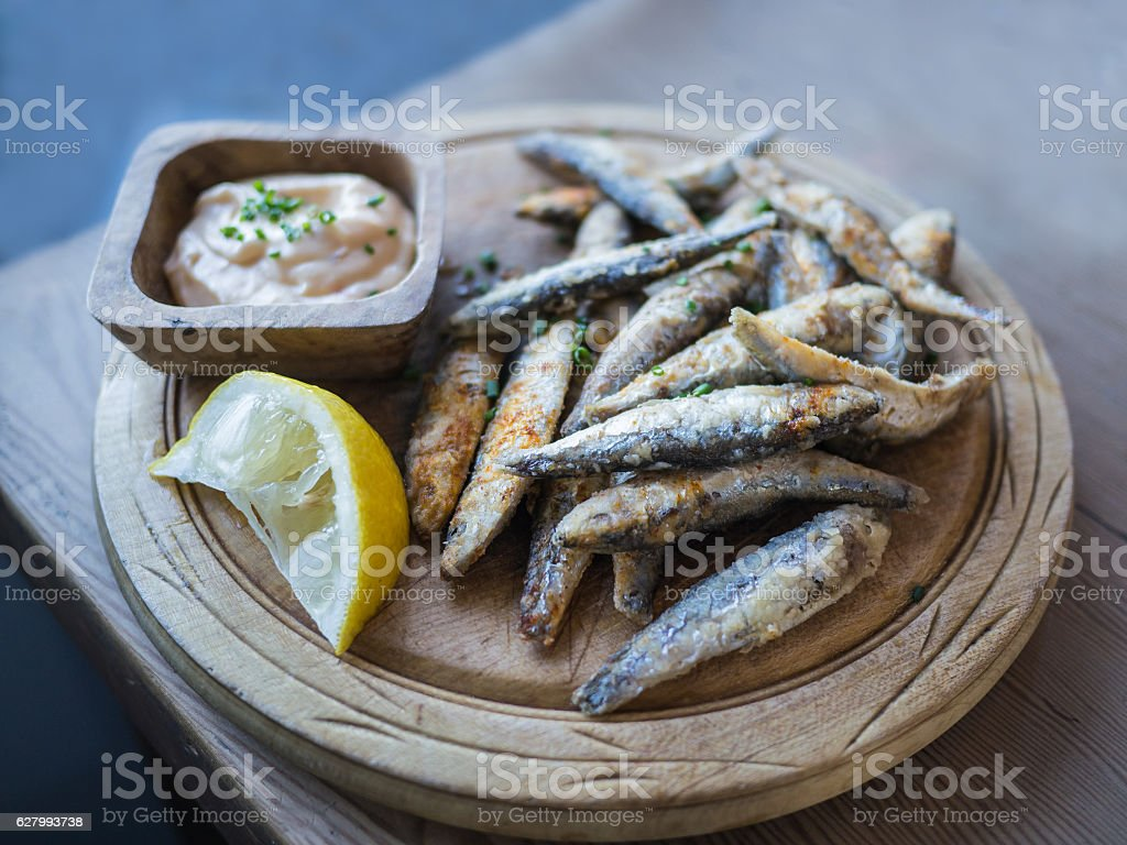 Whitebait served on a wooden platter stock photo