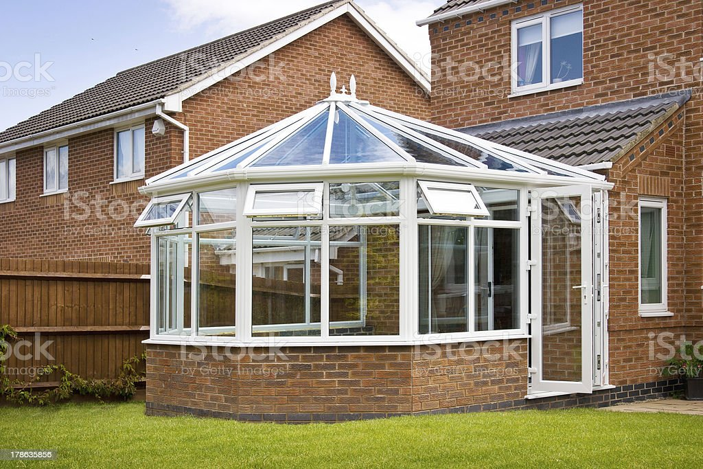 White-framed glass conservatory attached to house stock photo