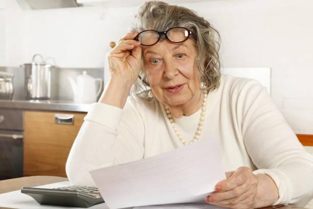Weißhaarige alte Dame, die mit einem Taschenrechner durch Quittungen schaut – Foto