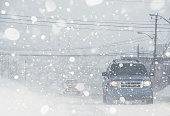 Motorists navigate a city street in white out conditions.
