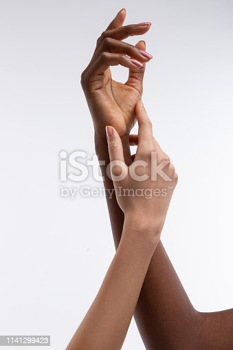 istock White-skinned woman touching hand of African-American friend 1141299423