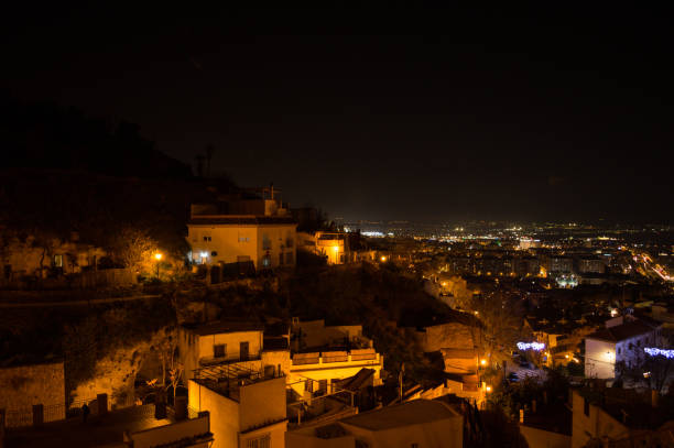 Whitewashed Houses and Cityscape in Granada, Spain as seen from Barranco del Abogado at Night stock photo