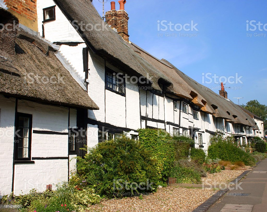 Whitewashed thatched medieval cottages in an English village stock photo