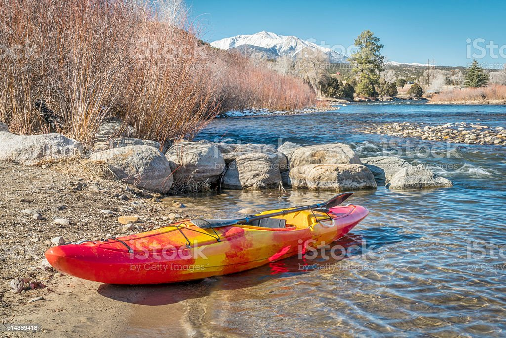whitewater kayak on river shore stock photo
