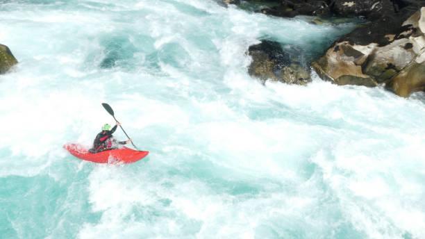 Whitewater kayaker paddles through rapids stock photo