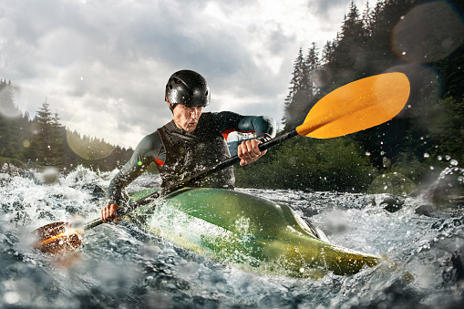 Whitewater kayaking, extreme kayaking. A guy in a kayak sails on a mountain river