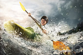 Whitewater kayaking, extreme kayaking. A fit woman in a kayak sails on a mountain river
