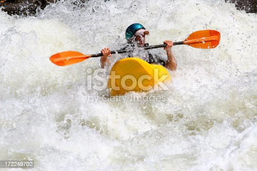 Whitewater boater breaks through a class five wave for air.