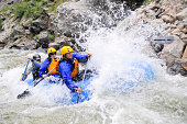 Group of men and women white water river rafting in a forested valley in Japan.