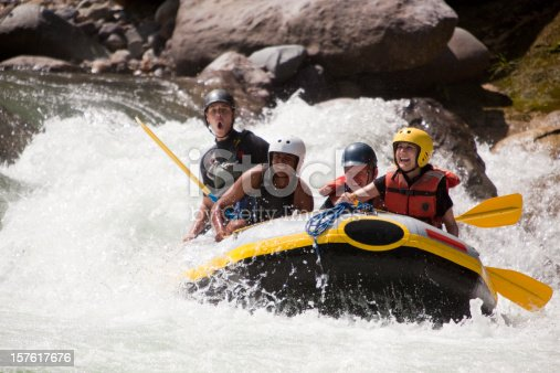 Happy group of friends rafting through whitewater rapids. Rio Congrejal, Honduras